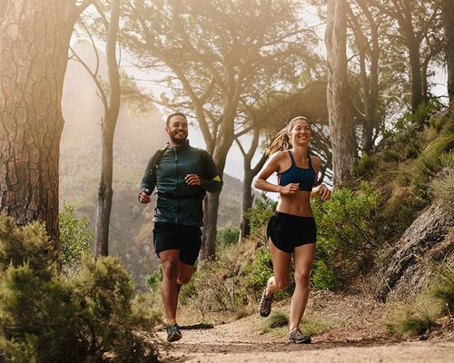 Couple jogging on a forest trail.