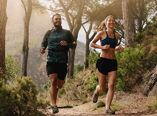 Couple running on a forest trail.