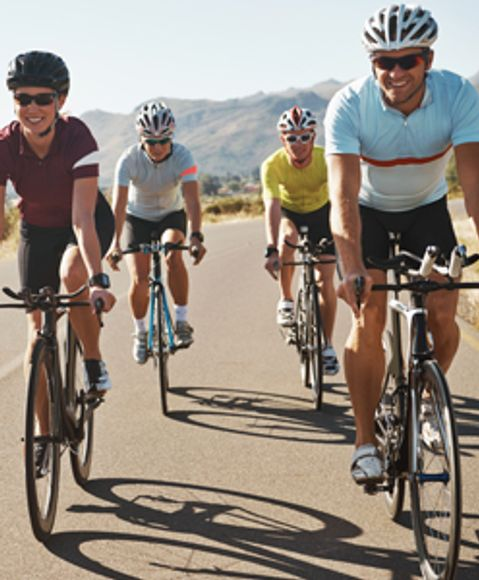 Group of cyclists riding on an open road in the desert