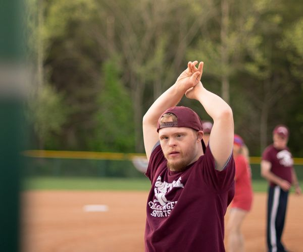 A child wearing a Burgandy baseball outfit with his hands raised above his head