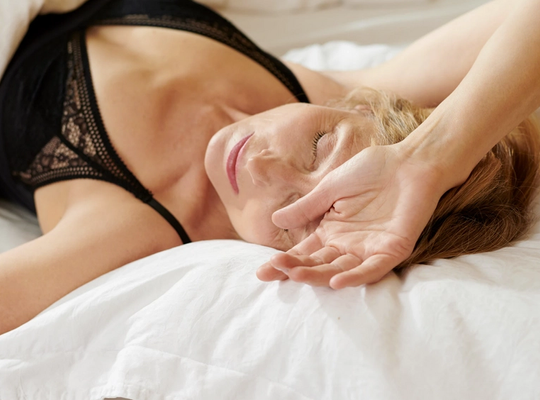 A women in discomfort laying in a white bed with her hand on her head
