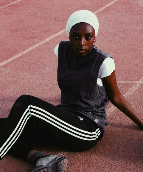 A woman in a green headscarf sitting on a running track looking at the camera