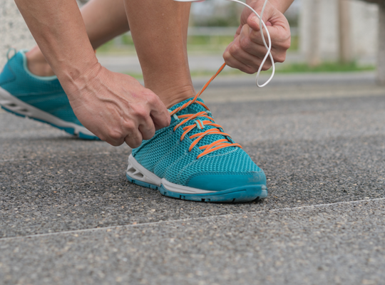woman ties her shoelaces - sweaty feet