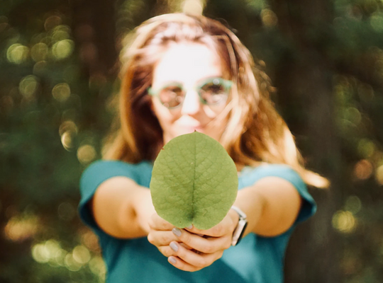 a women outside in the sun wearing glasses holding a leaf in front of her