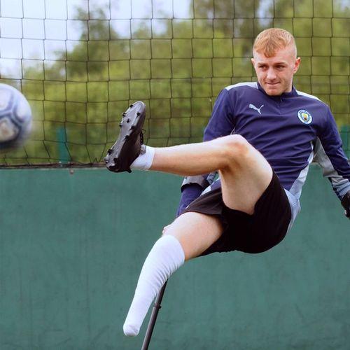 Sean kicking a football