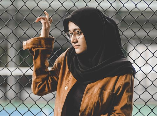 A girl in a brown jacket looking nervous by a chain link fence