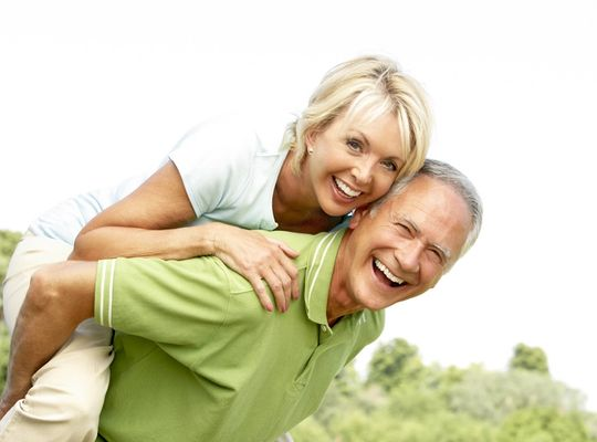 Older couple having fun as the man carries the woman in a piggy back