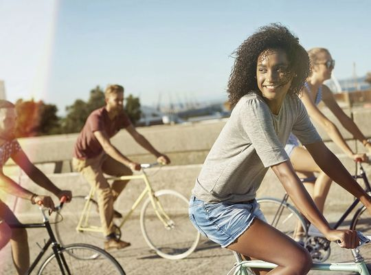 Group of young people smiling and moving while cycling