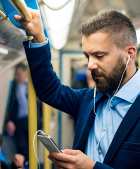 Man looking at his phone during his daily commute.