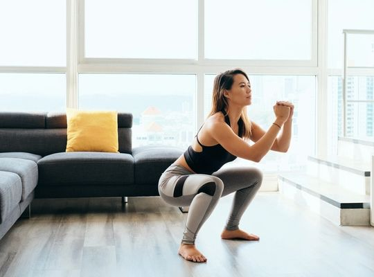 woman stretches during a workout in her apartment.