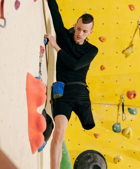 A man with a physical disability, working his way along a climbing wall
