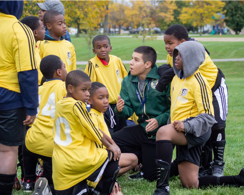 Team of young soccer players receiving team talk from coach
