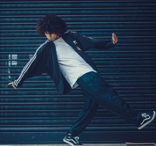 Hombre en ropa casual bailando en la calle en frente de unas contraventanas El mismo hombre bailando en la calle pero en otra pose