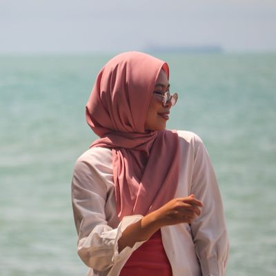 A lady wearing a headscarf standing by the sea