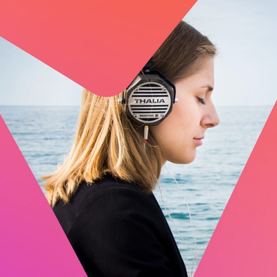 woman with eye closed listening to headphones in front of the sea