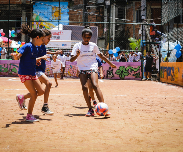 Young girls playing soccer on a sandy soccer pitch