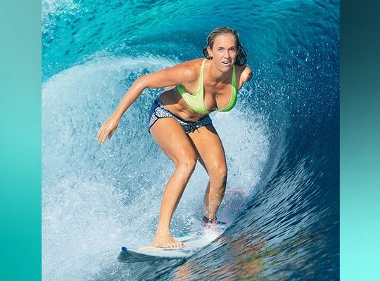 Bethany surfing on a blue wave