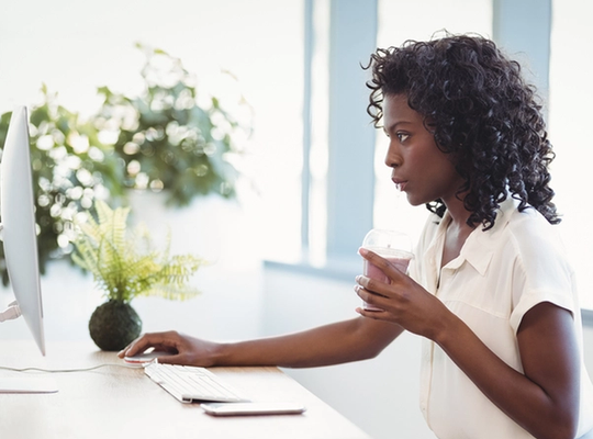 Woman drinks at her desk