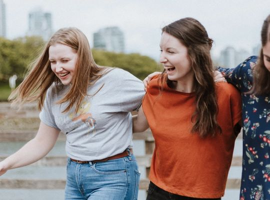 Three women laughing in front of a river, wave goodbye to white marks