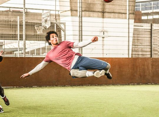 Man playing soccer volleys the ball mid air.