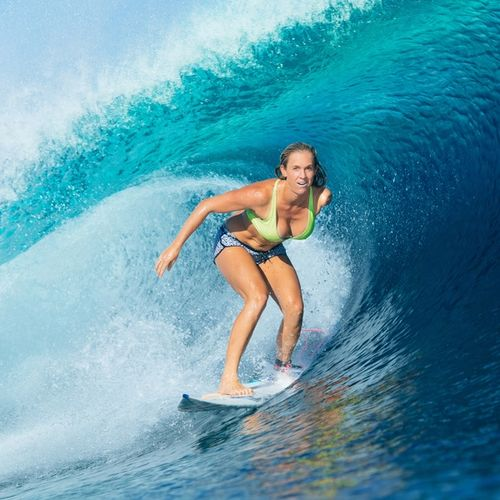 Bethany surfing on a crest of a blue wave
