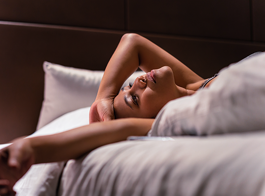 Woman lies on bed suffering from Night Sweats