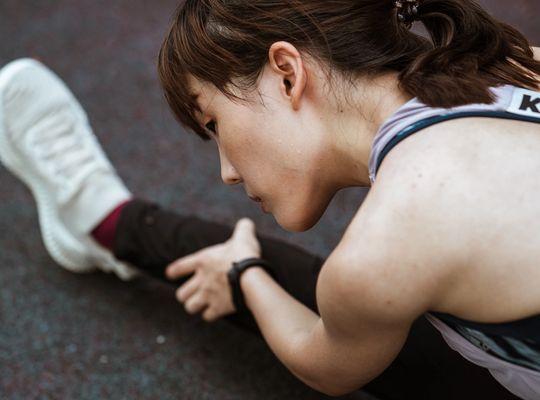 Mujer en ropa deportiva que se extiende antes de correr