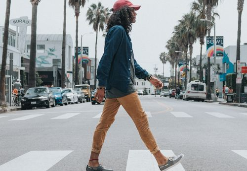 Man in a red baseball cap and long sleeve shirt and trousers, crossing the road