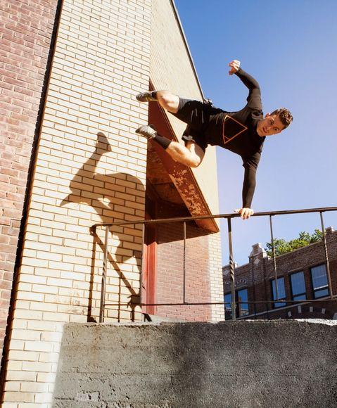 Man jumping over a railing during parkour move