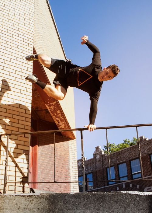 Man jumps over stairs performing parkour in an urban environment