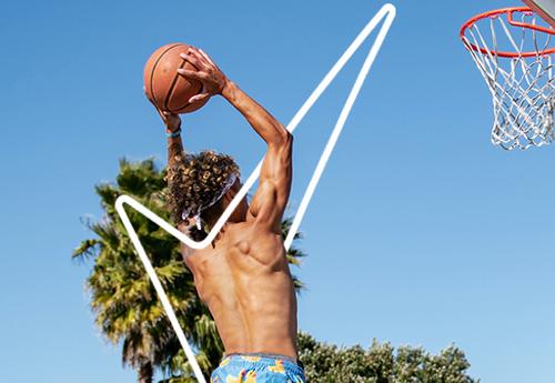 Topless man mid basketball dunk