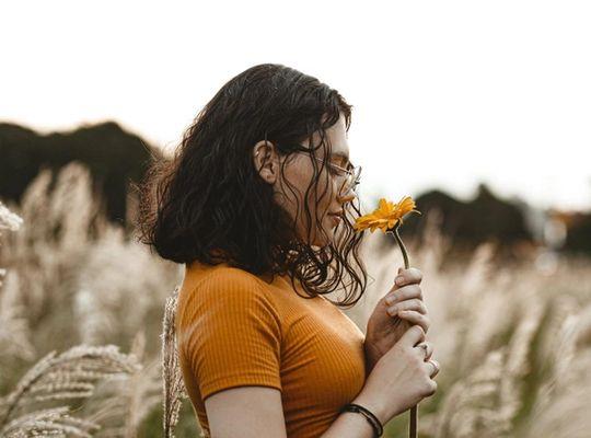 Woman smelling an orange flower in a field