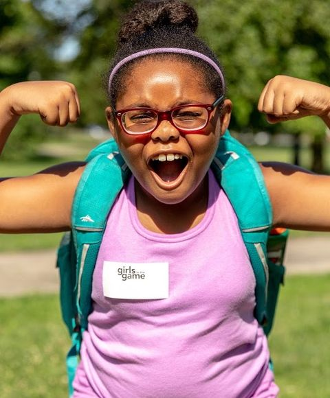 A young girl from Girls Game jokes as she flexes her biceps in the park