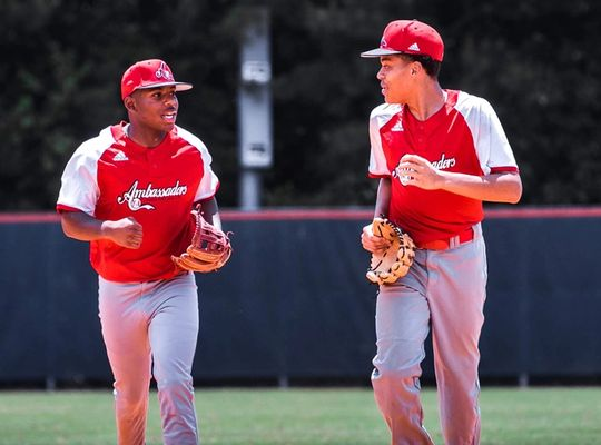 Two baseball players in red jersey's running and talking