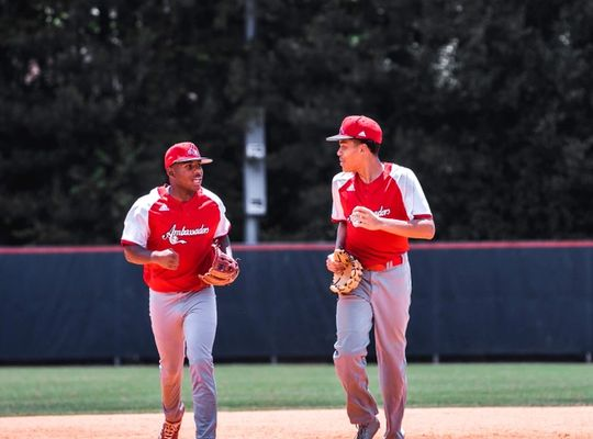 2 Baseball players between plays jog and chat at the same time.