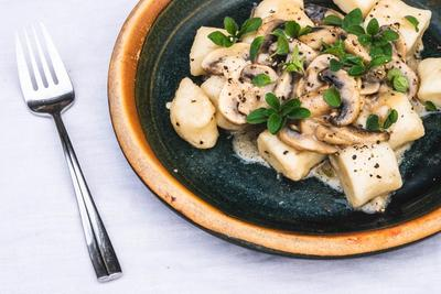 Gnocchi med svampe vendt i fløde og frisk oregano