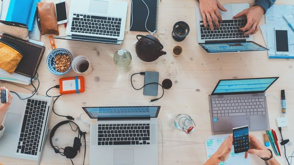 A picture of a working desk with many laptops