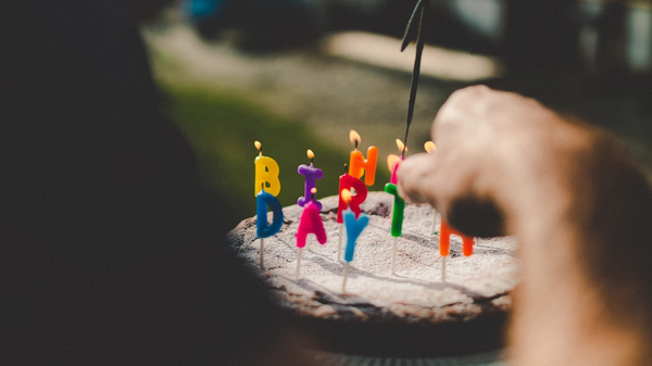 A hand lighting a candle on a cake decorated with letter candles spelling out Happy Birthday