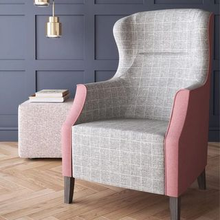 Pink and gray chair with books on side stool