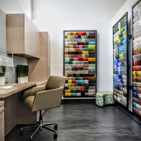 Two walls of sample fabrics and a desk with a chair