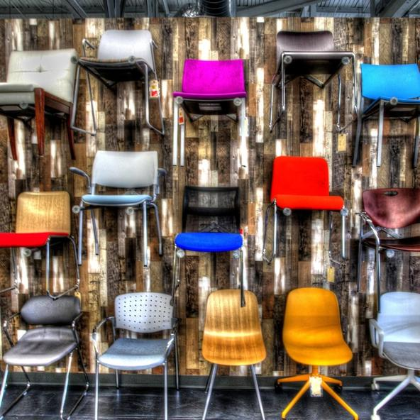 Chairs mounted on a wall in a showroom each chair is a different color