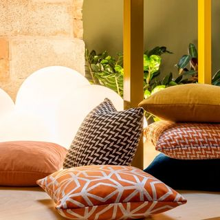 Pillows in a variety of fabrics by globe lights