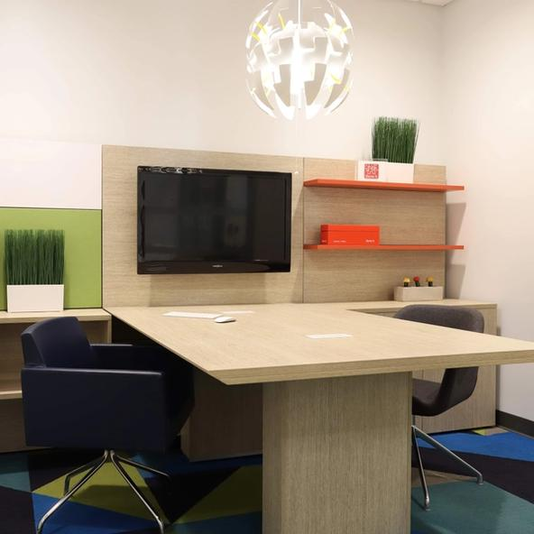 Three H desk that is light wood with a green plant, a mounted black monitor, and two chairs