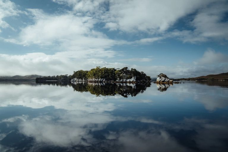 island with blue sky and clouds reflected in the water