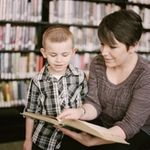 Woman teaching young child with a book in library