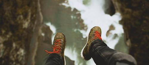 closeup of legs dangling over a precipice with jeans and hiking boots in the foreground and a long drop to rocks below