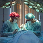 Surgeon and assistant in operating theater