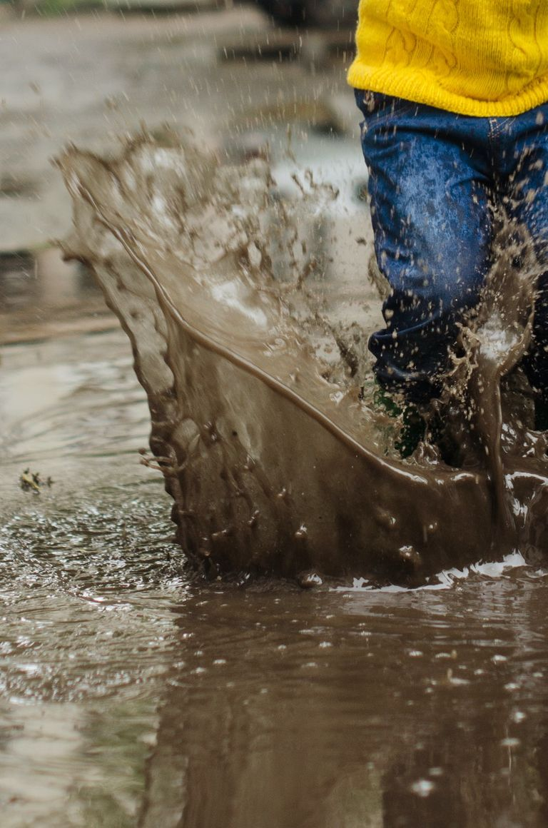 child splashing in muddy puddle with umbrella