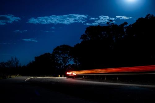 Car driving in the dark followd by light stripe
