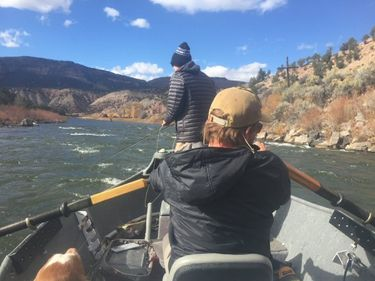 Fly fishing guide rowing a client down the Roaring Fork River